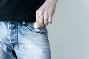 Deadly pack. Close-up of man putting a pack of narcotic into the pocket
